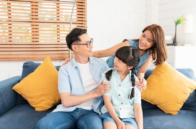 Famiglia asiatica felice che abbraccia insieme sul divano di casa soggiorno.
