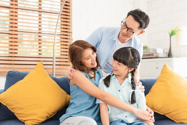 Famiglia asiatica felice che abbraccia insieme sul divano nel soggiorno di casa.