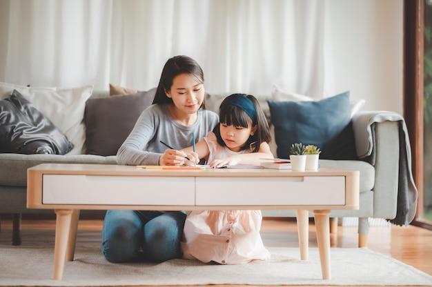 Felice famiglia asiatica, madre e figlia studiano o disegnano insieme a casa in soggiorno