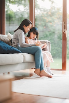 Felice famiglia asiatica madre e figlia utilizzando la tavoletta digitale per studiare insieme a casa.