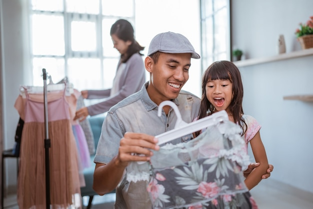 Felice famiglia asiatica che fa shopping insieme nel negozio di abbigliamento