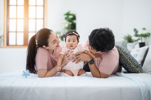 Felice famiglia asiatica seduta nella camera dei bambini a casa