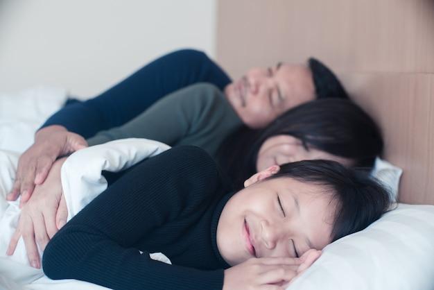 Famiglia asiatica felice che dorme in un letto comodo a casa