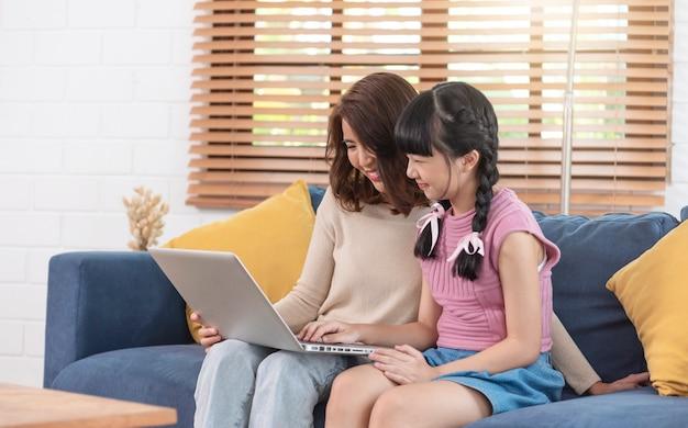 Felice famiglia asiatica che utilizza computer portatile insieme sul divano nel soggiorno di casa.