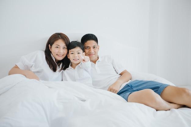 Famiglia asiatica felice con il figlio a casa sulla camera da letto che gioca e che ride