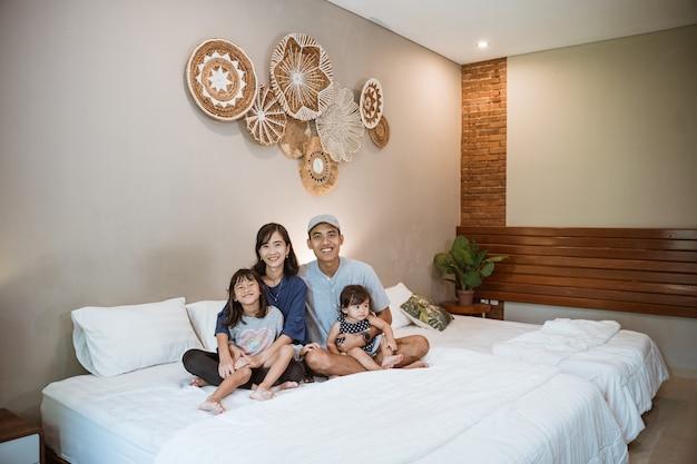 Felice famiglia asiatica con due bambini trascorrono il loro tempo insieme in camera da letto