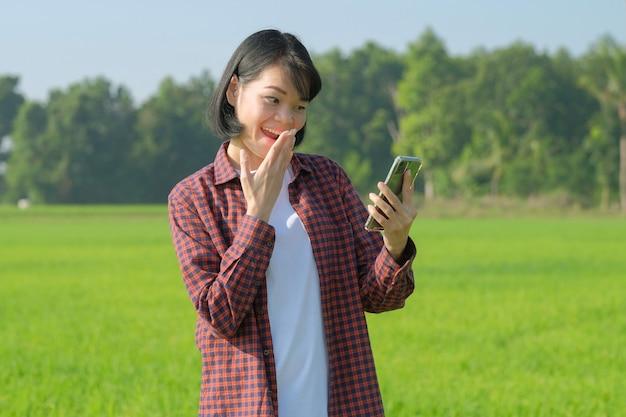 Donna asiatica felice dell'agricoltore che osserva smartphone con il fronte di sorpresa felice di wow alla fattoria verde