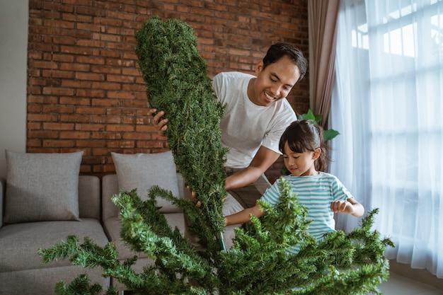 Felice padre asiatico e figlia che decorano l'albero di natale