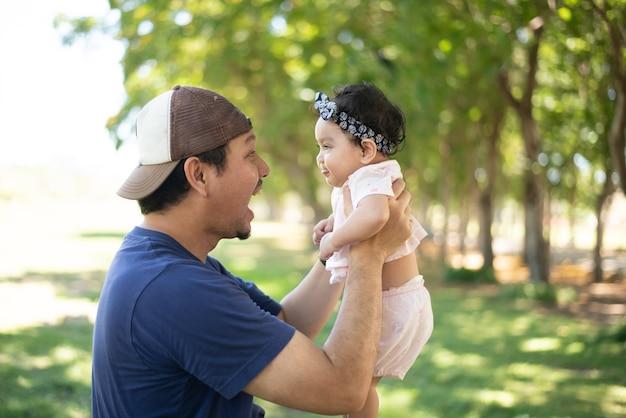 Padre asiatico felice che tiene in mano una bambina carina su sfondo sfocato di giardino verde