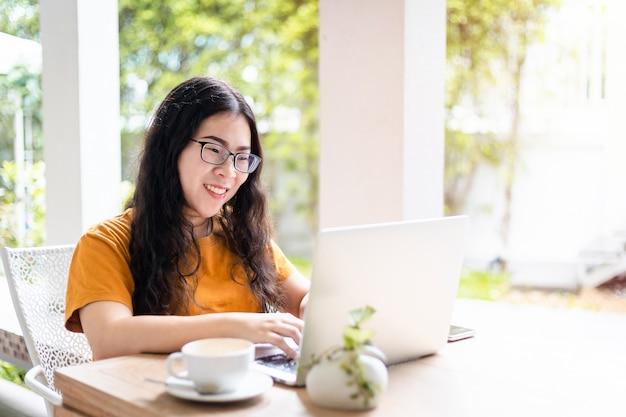 Felice della gente asiatica freelance business casual femminile che lavora con il computer portatile con la tazza di caffè e lo smartphone nella caffetteria come lo sfondo
