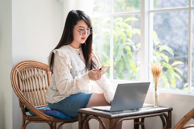 Felice di persone freelance asiatiche imprenditrice scrivendo un messaggio su smartphone casual lavorando con un computer portatile con una tazza di caffè al bar, business lifestyle