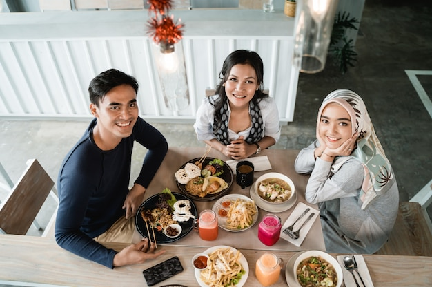 Amici asiatici felici pranzando insieme