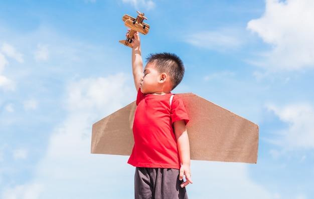 Felice asiatico divertente bambino o ragazzino ragazzino sorriso indossare cappello pilota gioca e occhiali con ala di aeroplano di cartone giocattolo volare tenere aereo giocattolo all'aperto contro nuvola di cielo blu estate, libertà di avvio