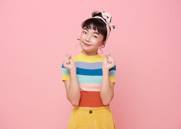 Mano asiatica felice della ragazza che mostra il mini gesto del cuore sopra fondo rosa.