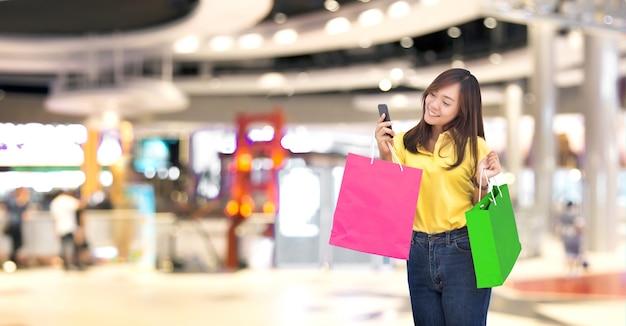 La ragazza asiatica felice resive l'ordine nella borsa della spesa di carta con lo shopping online tramite smartphone nel nuovo stile di vita digitale normale (includere il percorso di residuo della potatura meccanica)