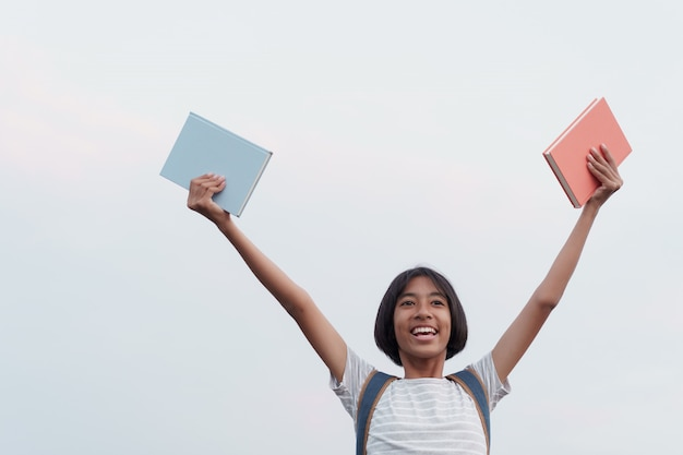 La ragazza asiatica felice sorride sul fronte mentre tiene un libro e una mano sollevati su