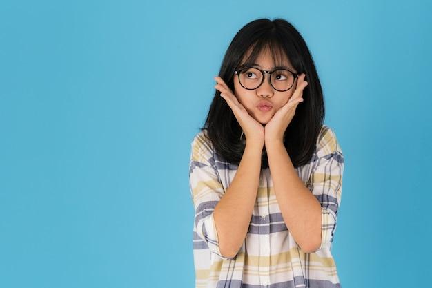 Felice ragazza asiatica in piedi con gli occhiali su sfondo blu