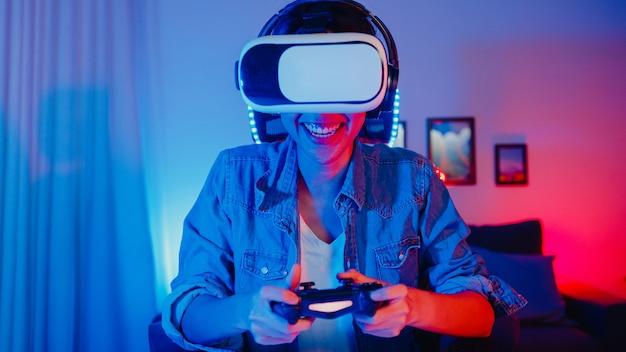 Felice ragazza asiatica che indossa occhiali per realtà virtuale occhiali auricolare con espressione di sorpresa