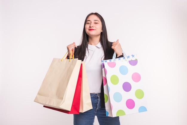 Ragazza asiatica felice con le labbra rosse che tengono i sacchetti della spesa su bianco