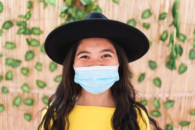 Donna asiatica felice dei pantaloni a vita bassa che porta maschera protettiva