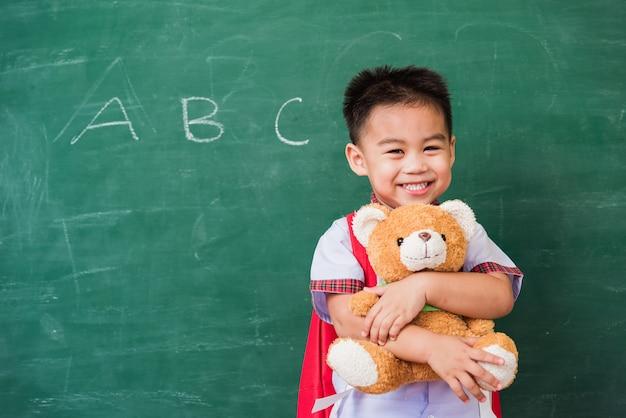 Piccolo bambino asiatico felice dall'asilo in uniforme dello studente con il sacchetto di scuola che sorride e che abbraccia l'orsacchiotto