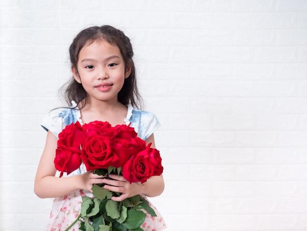 Piccola ragazza sveglia asiatica felice che sta e che tiene il mazzo della rosa rossa sopra la parete di mattoni bianca.
