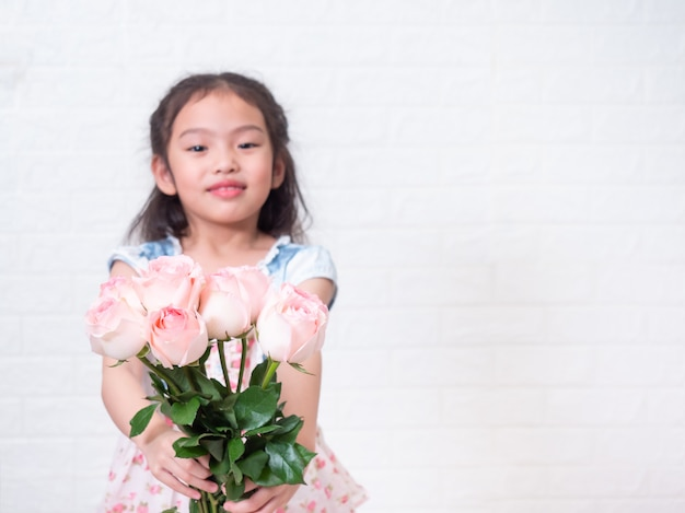 La piccola ragazza sveglia asiatica felice che sta e che tiene il mazzo rosa fiorisce sopra la parete di mattoni bianca. messa a fuoco selettiva a rosa.