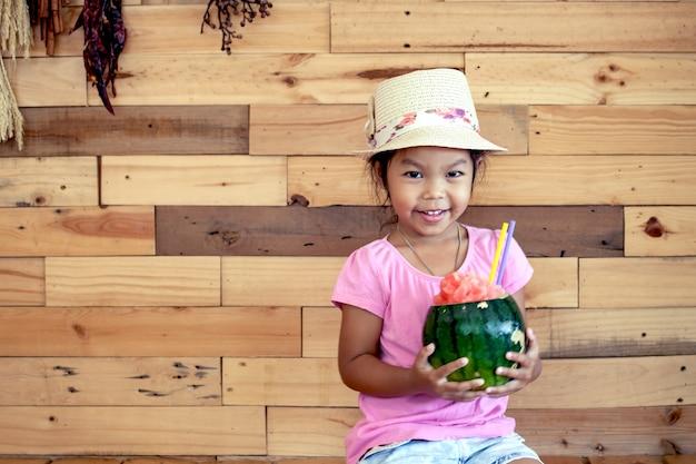La bambina asiatica felice sta tenendo il succo mescolato anguria su fondo di legno