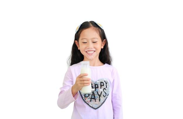 Felice ragazza asiatica ragazzino bere latte dalla bottiglia di vetro isolato su bianco