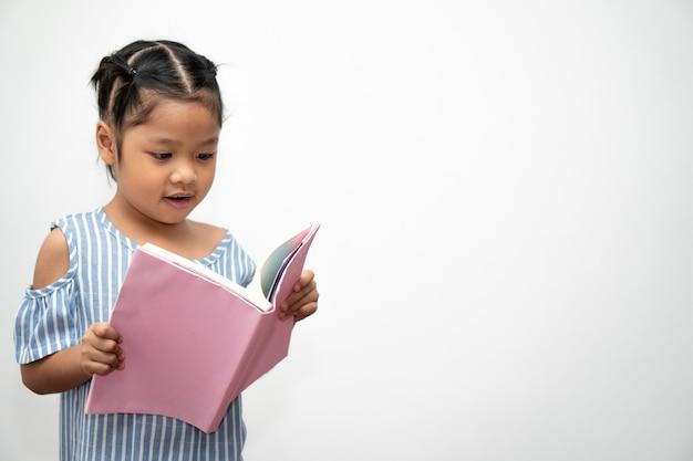 Felice bambina asiatica in età prescolare che tiene e legge un libro su sfondo bianco isolato. concetto di bambino della scuola e educazione nelle scuole elementari e in età prescolare