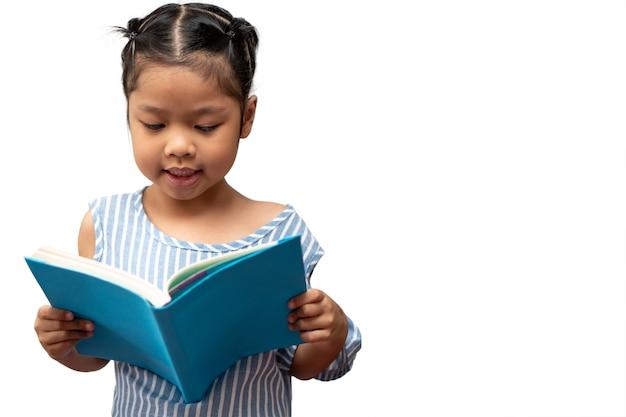 Felice bambina asiatica in età prescolare che tiene in mano e legge un libro su sfondo bianco isolato