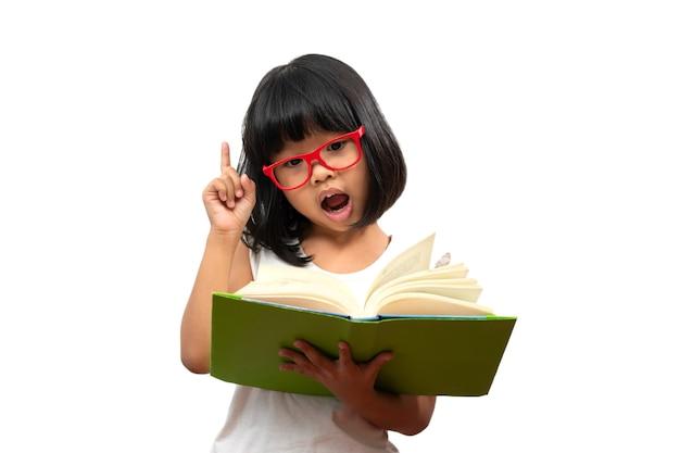 Felice bambina asiatica in età prescolare con gli occhiali rossi in possesso di un libro verde e pollice in alto su sfondo bianco isolato. concetto di scolaro e educazione nella scuola elementare e prescolare, scuola a casa