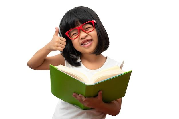 Felice bambina asiatica in età prescolare che indossa occhiali rossi con in mano un libro verde e pollice in alto su bianco