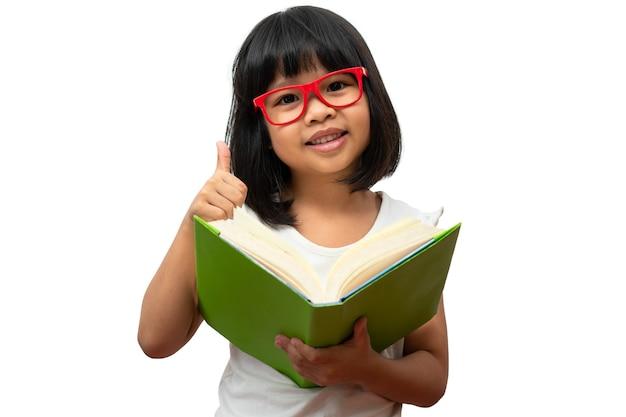 Felice bambina asiatica in età prescolare che indossa occhiali rossi con in mano un libro verde e pollice in alto
