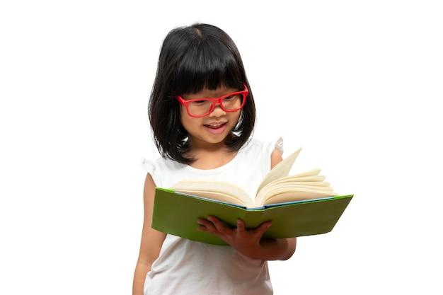 Felice bambina asiatica in età prescolare con gli occhiali rossi che tiene e legge un libro verde su sfondo bianco isolato. concetto di scolaro e educazione nella scuola elementare e prescolare, scuola a casa