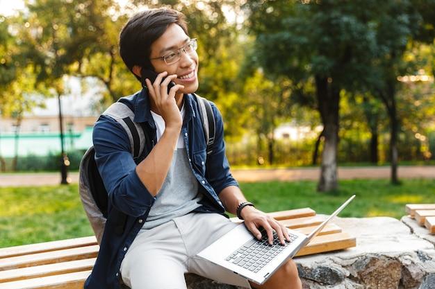 Felice studente maschio asiatico in occhiali parlando da smartphone mentre era seduto sulla panchina nel parco con il computer portatile