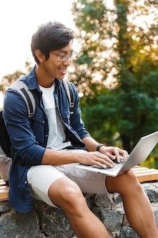 Felice studente maschio asiatico in occhiali utilizzando il computer portatile mentre era seduto su una panchina nel parco