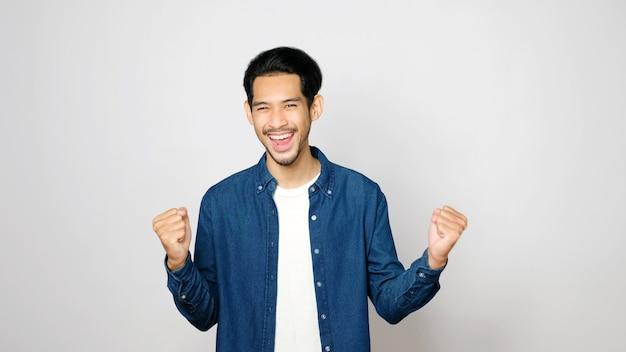 Felice uomo asiatico braccio in alto con successo guardando la fotocamera mentre in piedi su sfondo grigio isolato