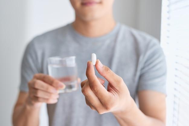 Uomo asiatico felice che tiene una pillola e un bicchiere d'acqua che guarda l'obbiettivo