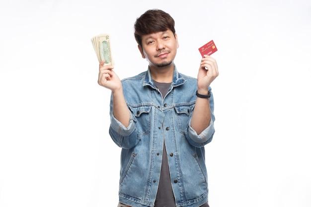 Felice uomo asiatico nella faccina sorridente che tiene una carta di credito e una banconota in dollari, guarda la telecamera, ritratto di luce studio isolato su sfondo bianco, concetto di carta di credito