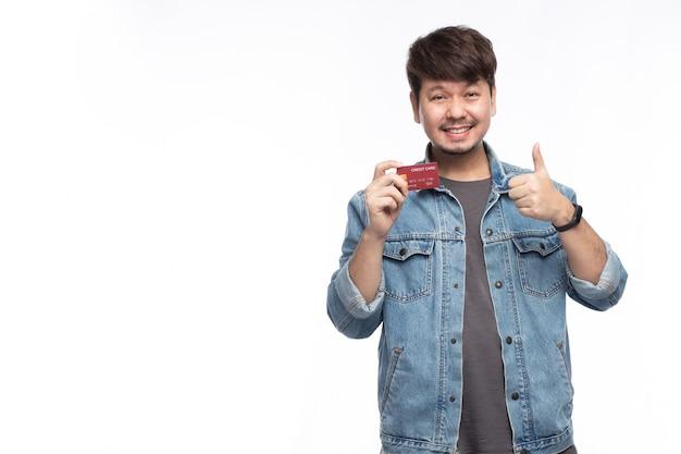 Felice l'uomo asiatico nella faccina sorridente in possesso di una carta di credito, pollice in alto, guarda la telecamera, studio ritratto di luce isolato su sfondo bianco, concetto di carta di credito