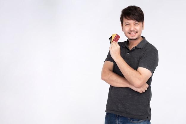 Felice l'uomo asiatico nella faccina sorridente tenendo tre carte di credito, guarda la telecamera, studio ritratto di luce isolati su sfondo bianco, carta di credito concept