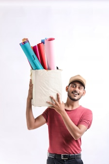 Felice uomo asiatico in t-shirt e berretto con scatola di carta colorata isolata su sfondo bianco, concetto di servizio di consegna
