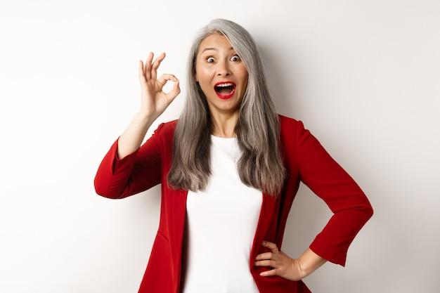 Felice donna matura asiatica in giacca rossa che mostra il segno giusto, sorridendo stupita, lodando qualcosa di fantastico, in piedi su sfondo bianco.