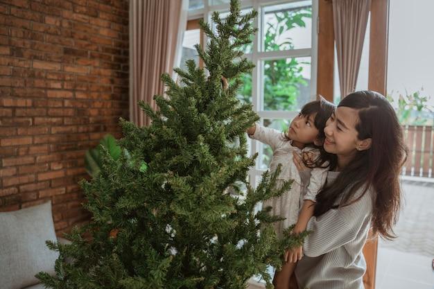 Felice asiatica madre e figlia che decorano l'albero di natale