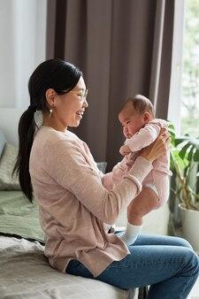 Felice madre asiatica seduta sul letto tenendo in braccio la sua neonata e ridendo mentre gioca con lei in ...