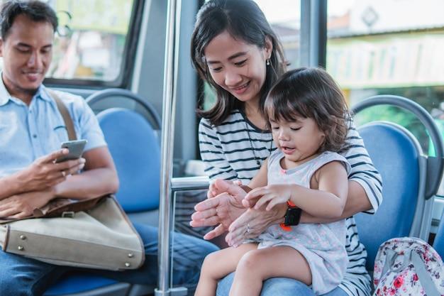 Felice madre asiatica che porta sua figlia in sella ai mezzi pubblici