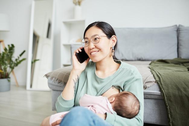 Felice madre asiatica che parla al cellulare mentre dà da mangiare al suo bambino seduto in soggiorno