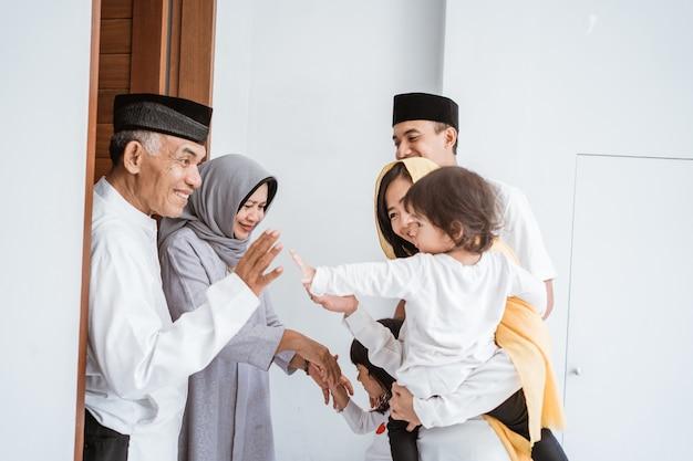 Felice coppia di età compresa tra musulmani asiatici incontro bambini e nipoti a due passi durante la celebrazione di eid mubarak