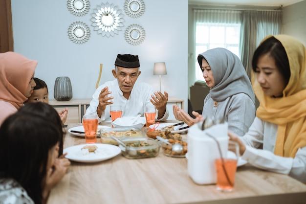 Famiglia musulmana asiatica felice che prega prima del loro pasto iftar durante il digiuno del ramadan